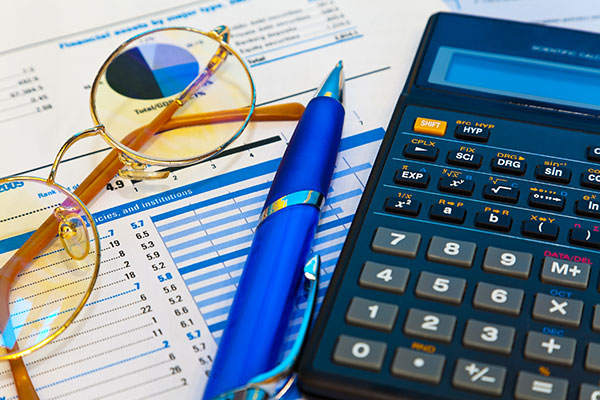 financial documents alongside a calculator and glasses